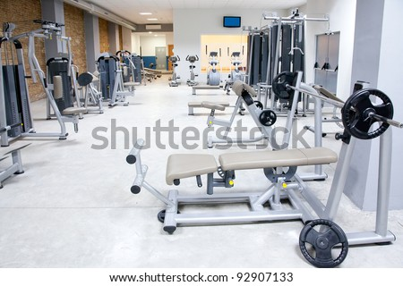 Fitness club gym with sport equipment modern interior - stock photo