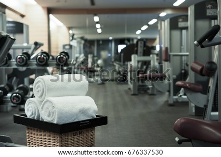 Fitness club in luxury hotel interior. Focus on white towels.