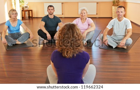 Fitness coach giving group yoga instructions in a gym - stock photo