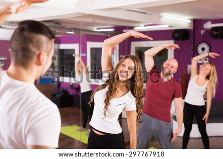 Fitness coach showing to adult happy learners new exercise at class