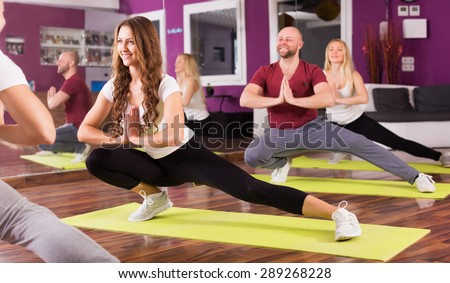 Fitness coach showing to adult positive learners new exercise at class - stock photo