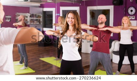 Fitness coach showing to happy learners new exercise at class - stock photo