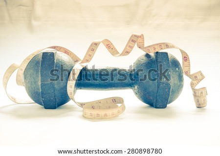 Fitness concept - dumbbell with measuring tape with vintage retro picture style