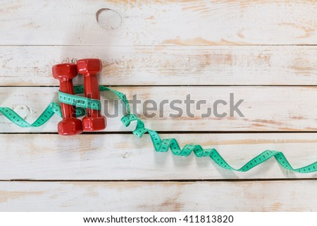 Fitness concept with dumbbells and measuring tape - stock photo