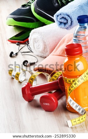 Fitness concept with dumbbells, fruits juice and sportswear - stock photo