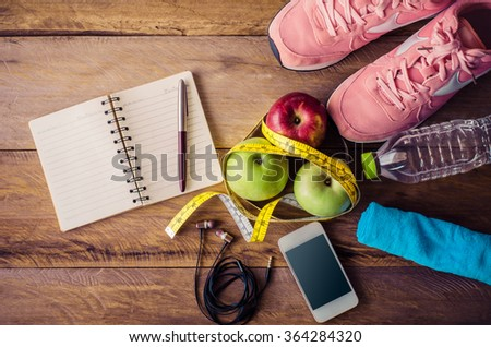 fitness concept with Exercise Equipment on wooden background. - stock photo