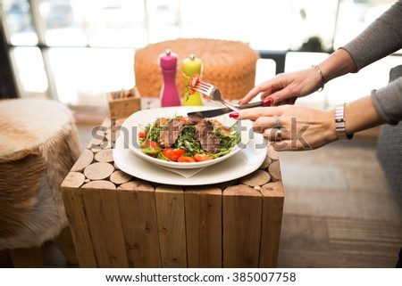 Fitness concept with healthy dieting and healthy lifestyle.Diet,health and nutrition.Eating salad with beef.Red tomatoes,rocket and meat protein diet meal.Woman eating healthy salad in restaurant  - stock photo