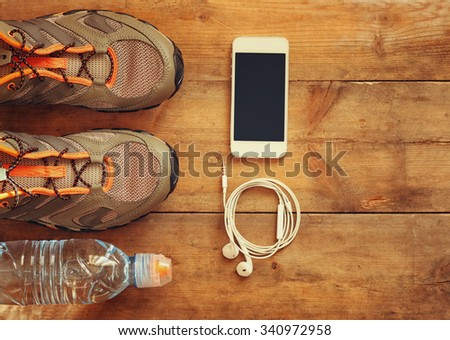 fitness concept with mobile phone  and sport footwear over wooden background.. top view image