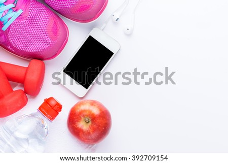 fitness concept with mobile phone, towel, shoes, dumbbells, red apple and woman sport footwear over white background. View from above - stock photo