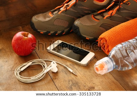 fitness concept with mobile phone with earphones, towel, apple and sport footwear over wooden background. - stock photo