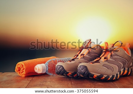 fitness concept with sport footwear, towel and water bottle over wooden table in front of sunset landscape.  - stock photo