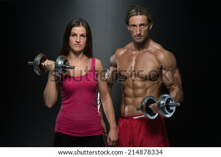 Fitness Couple Exercise Biceps - Strong Young Couple Working Out With Dumbbells - Shot In Studio On A Black Background - stock photo