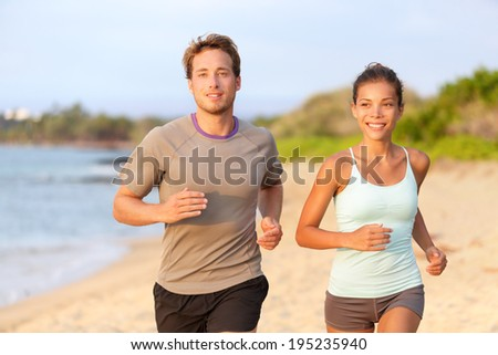 Fitness couple jogging outside on beach smiling in summer sunset. Young mixed race asian female model running on beach with handsome caucasian male.