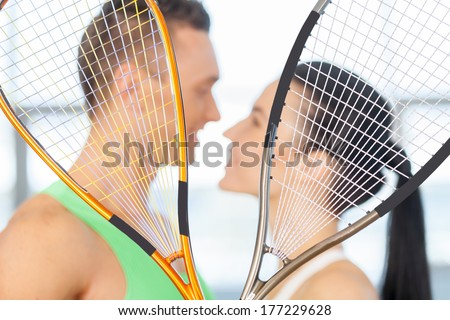 Fitness couple. Loving couple kissing behind tennis racket - stock photo