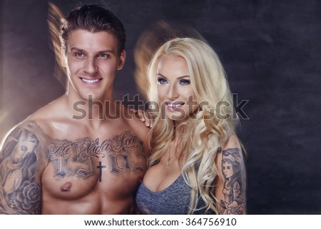 Fitness couple of smiling shirtles tattooed man and sensual blond woman. - stock photo