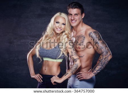 Fitness couple. Shirtless tattooed muscular man and awesome blond female in sportswear over grey background. - stock photo