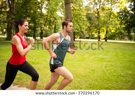 Fitness couple - young man and woman jogging outdoor in nature - stock photo