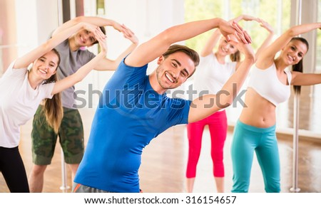 Fitness dance studio class. Group of people are exercising in dance studio.