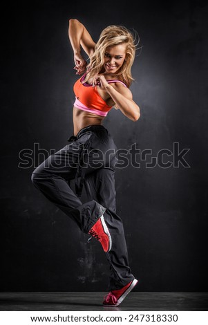 Fitness dancer girl in passionate pose on gray background - stock photo