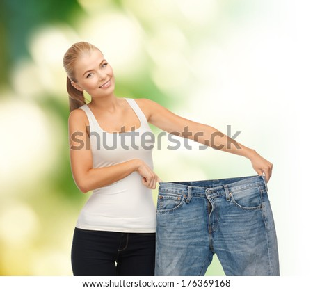 fitness, diet and good shape concept - sporty woman showing big pants - stock photo