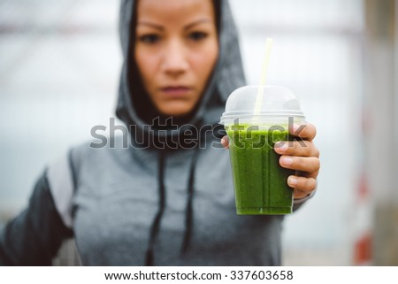 Fitness diet and nutrition concept. Tough looking urban sporty woman taking a rest for drinking nutritive detox smoothie. - stock photo