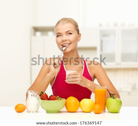fitness, diet, health and food concept - young woman eating healthy breakfast