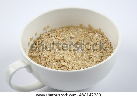 Fitness diet healthy Breakfast which included oatmeal oat porridge in a cup isolated on white.