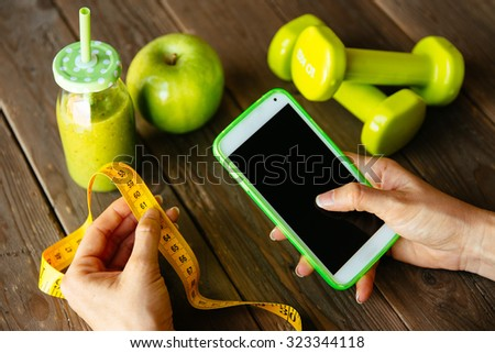 Fitness diet nutrition and workout routine smartphone app concept. Healthy green detox, apple and dumbbells for slimming down dieting. Female checking weight loss with measuring tape. - stock photo