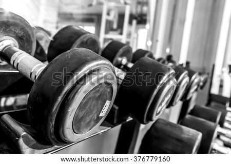 fitness dumbbells, weights equipment, selective focus, fitness club, black and white photography - stock photo