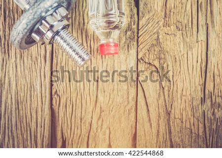 fitness equipment : drumbellsl and water bottle on old wood table - stock photo