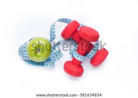 Fitness equipment. Healthy food. Apple, dumbbells and measuring tape on white background. View from above - stock photo