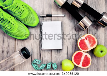 Fitness equipment. Healthy food. Sneakers, water,apple  on wooden background - stock photo