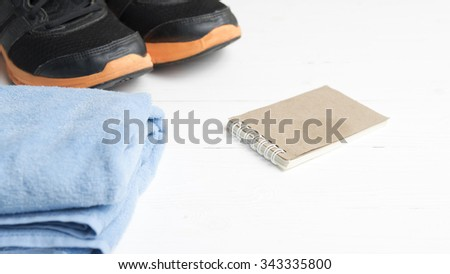 fitness equipment : running shoes,blue towel and notepad on white wood table