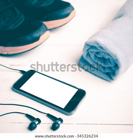 fitness equipment:running shoes,blue towel and smart phone on white wood table vintage style