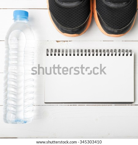 fitness equipment : running shoes,drinking water and notebook on white wood table