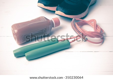 fitness equipment : running shoes,jumping rope and orange juice on white wood background vintage tone style
