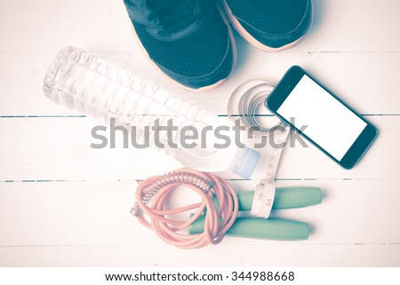 fitness equipment : running shoes,jumping rope,drinking water,measuring tape and phone on white wood table vintage style