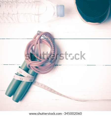 fitness equipment : running shoes,jumping rope,measuring tape and water bottle on white wood table vintage style