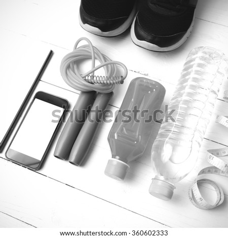 fitness equipment:running shoes,jumping rope,notepad,phone,water,juice and measuring tape on white wood background black and white color
