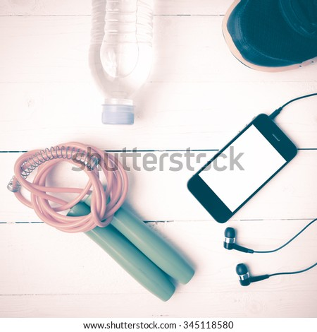 fitness equipment : running shoes,jumping rope,phone and water bottle on white wood table vintage style