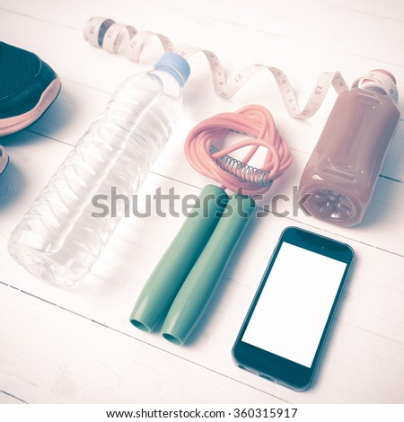fitness equipment:running shoes,phone,measuring tape,water,juice and jumpong rope on white wood background vintage style