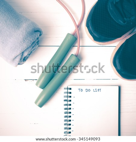 fitness equipment : running shoes,towel,jumping rope and notebook write to do list on white wood table vintage style