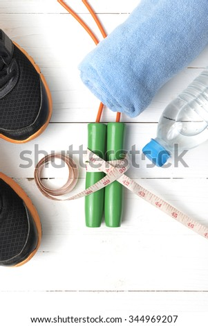 fitness equipment : running shoes,towel,jumping rope,water bottle and measuring tape on white wood table