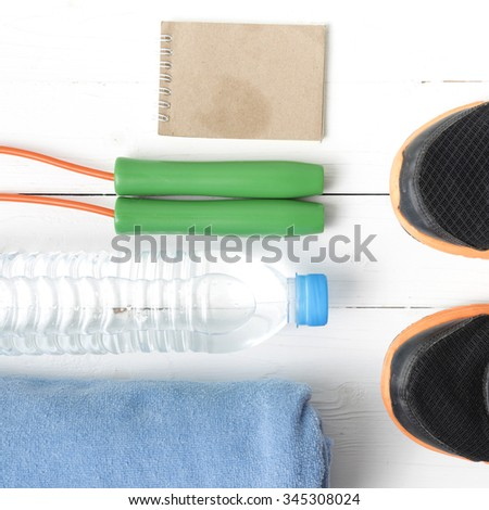fitness equipment : running shoes,towel,jumping rope,water bottle and notepad on white wood table