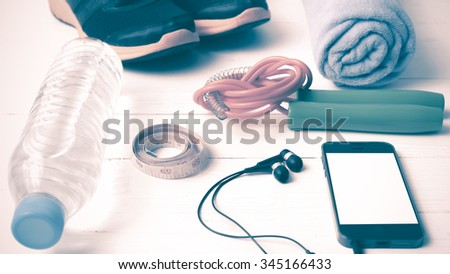 fitness equipment : running shoes,towel,jumping rope,water bottle,phone and measuring tape on white wood table vintage style