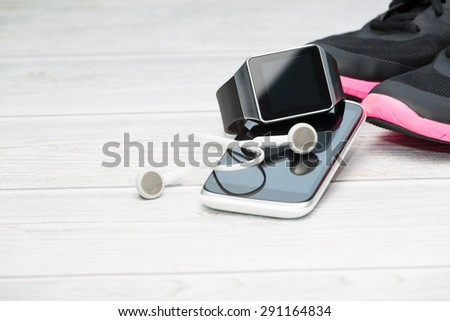 Fitness equipment, smart watch and phone on wood background. - stock photo