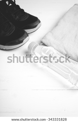 fitness equipment: towel,drinking water and running shoes on white wood table black and white color style