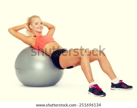 fitness, exercise and diet concept - smiling sporty woman exercising on fitness ball - stock photo
