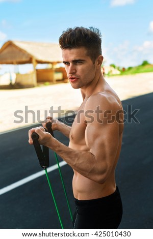 Fitness Exercise. Athletic Man With Fit Muscular Body Exercising During Outdoor Workout. Handsome Athlete Model Doing Expander Exercises And Training On Road In Summer. Sport, Active Lifestyle Concept