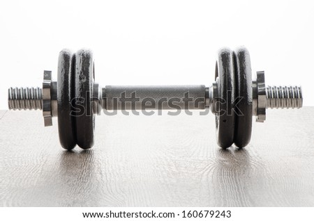 Fitness exercise equipment dumbbell weights on wood background.